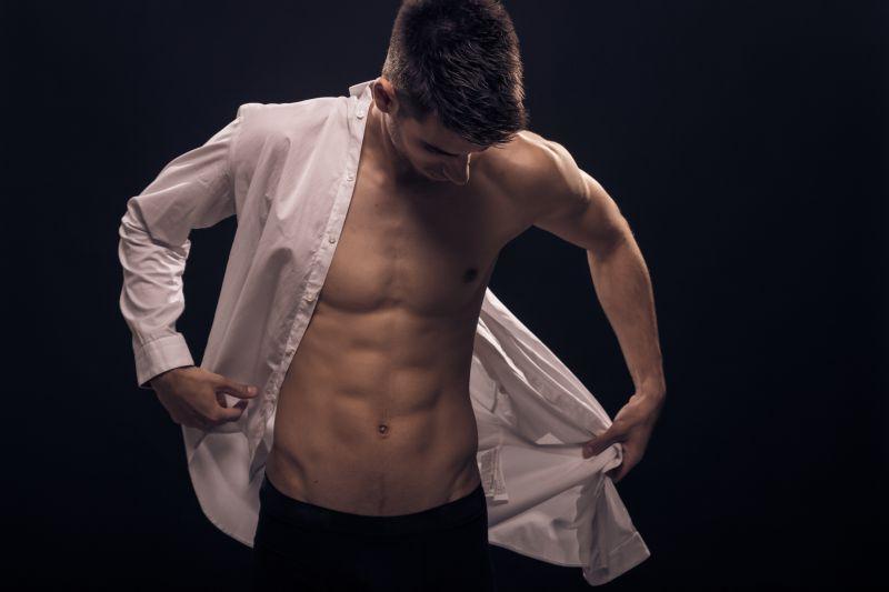 モテる細マッチョな男性がシャツを脱いでいる写真